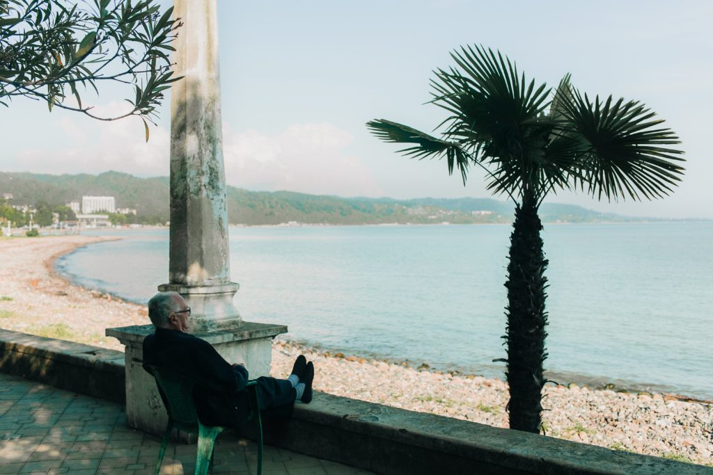 Man sitting by palm tree
